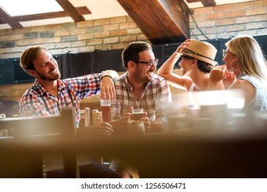 Young cheerful people in the beer pub drinking and having good time