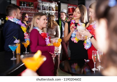 Young cheerful people with cocktails having fun on Hawaiian party at nightclub