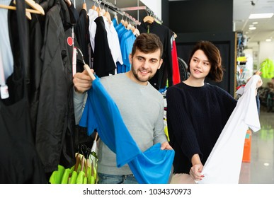Young cheerful positive  couple choosing sport shirt in bicycle shop