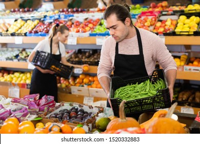 Young  cheerful positive smiling man with box of beans and woman wearing apron on background on the supermarket