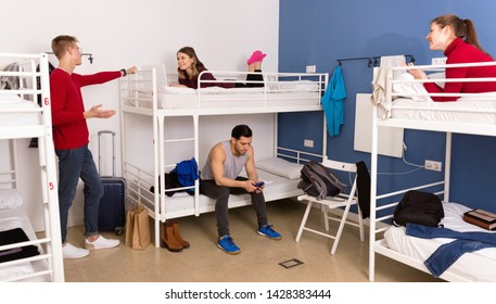 Young cheerful positive smiling men and women friendly interacting while staying in modern comfy hostel