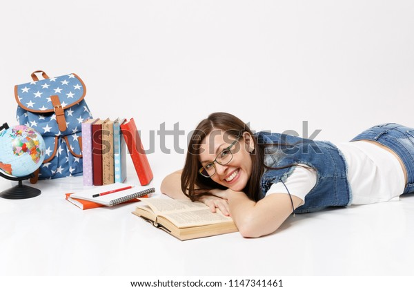 Young cheerful pretty woman student in denim clothes and glasses reading book lying near globe backpack, school books isolated on white background. Education in high school university college concept