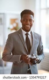 Young cheerful professional in elegant grey suit going to use photocamera in office