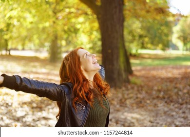 Young cheerful red-haired woman enjoying autumn day in park