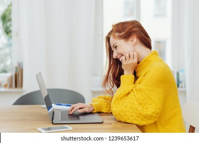 Young cheerful red-haired woman in yellow sweater using laptop
