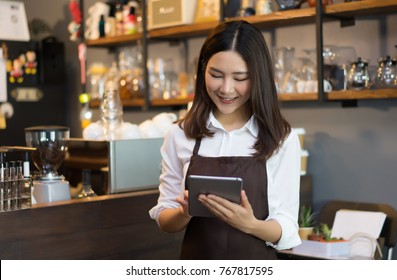 Young cheerful smiling barista using tablet in front of coffee shop counter bar, Service Concept.