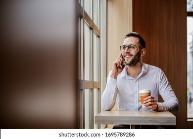 Young cheerful smiling man elegantly dressed sitting in cafeteria next to window, looking trough it, holding disposable cup of coffee and having phone conversation with a friend.