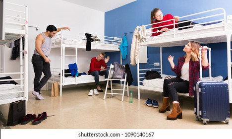 Young cheerful  smiling men and women friendly interacting while staying in modern comfy hostel