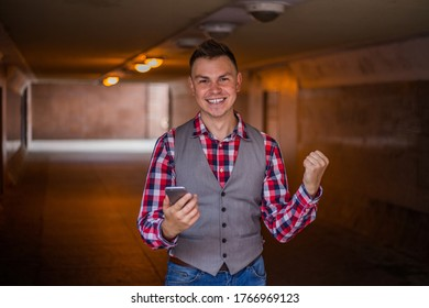Young cheerful stylish handsome guy rejoices event from smartphone