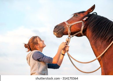 Young cheerful teenage girl calming big spirit chestnut horse. Vibrant multicolored summertime outdoors horizontal image.