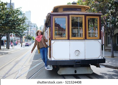 Young cheerful tourist taking a ride in famous cable car in San Francisco, California, USA