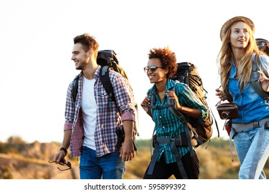 Young cheerful travelers with backpacks smiling, walking in canyon.