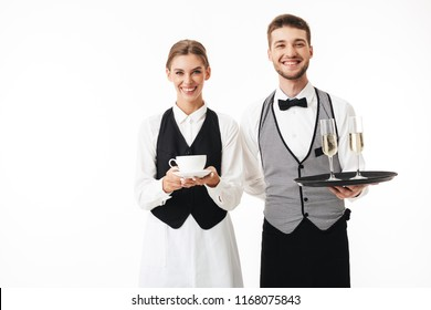 Young cheerful waiter holding tray with glasses of champagne and pretty waitress with cup of coffee in hands happily looking in camera together over white background