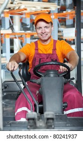 young cheerful warehouse worker driver in uniform driving forklift stacker loader