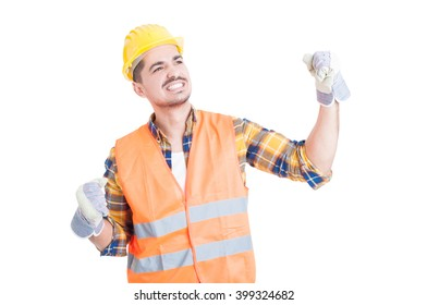 Young cheerful constructor wearing a hardhat and punching the air with his fist while celebrates a success or victory isolated on white studio background