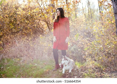 young cheerful woman in autumn park with siberian husky dog