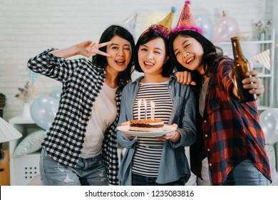 young cheerful woman blinking eyes face camera posing taking picture in decorated room for birthday house party. attractive ladies holding cake with candles on fire and beer wearing colorful hats.