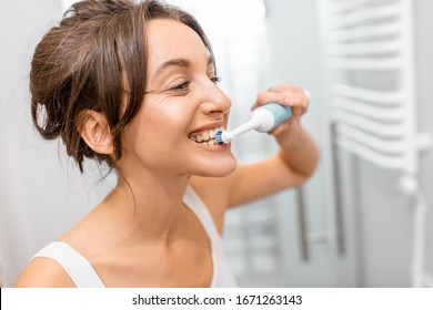 Young and cheerful woman brushing teeth with electric toothbrush during morning hygiene procedures in the bathroom, facial portrait