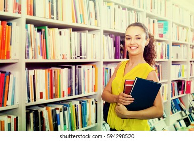 Young cheerful woman buying literature books in hard cover in bookstore