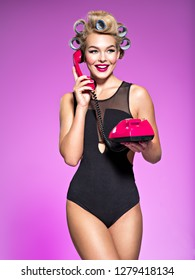 Young cheerful woman calling by retro phone. Girl with blue curlers talking by red telephone.  Portrain of an atractive female using a vintage phone.