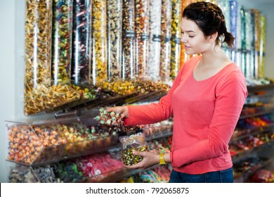 Young cheerful woman with candies at sweets shop