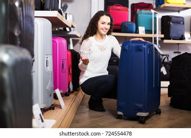 Young cheerful woman choosing travel suitcase in haberdashery shop