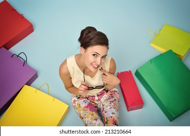 Young cheerful woman with colored paper shopping bags. Shopaholic. Shopping concept and ideas. Urban lifestyle. Image toned.
