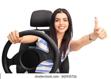Young cheerful woman driving a vehicle and giving a thumb up isolated on white background