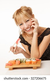 Young cheerful woman eating sushi with chopsticks