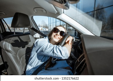 Young and cheerful woman enjoying new car hugging steering wheel sitting inside, wide angle view