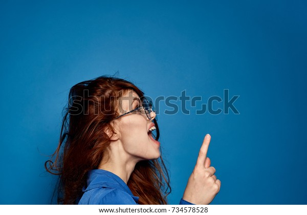 young, cheerful woman with glasses in profile shows finger on free place on blue background