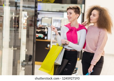 Young cheerful woman going along shopping centre with colourful paper bags showing something in the shop window to her blonde girlfriend, being fascinated by what she found.