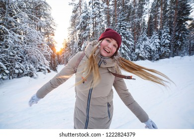 Young cheerful woman having fun winter in snow covered winter pine forest. Snowy weather. Big pines. Winter holidays.