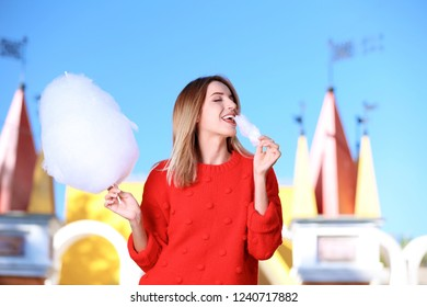 Young cheerful woman having fun with  cotton candy in amusement park