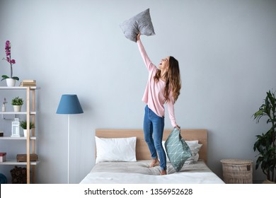 Young cheerful woman having fun with pillows on the bed at home. Lifestyle concept.