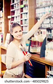 young cheerful woman holding paint color in tube in art shop
