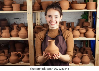 a young and cheerful woman holding a vase of clay. The potter works in a pottery workshop with clay. the concept of pottery mastery and creativity