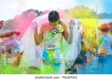 Young cheerful woman at Holi paint party in wedding dress