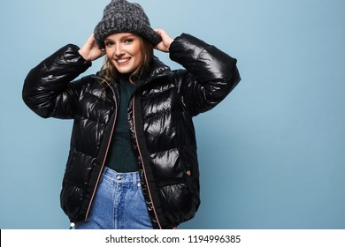 Young cheerful woman in knitted hat and black down jacket happily looking in camera over blue background