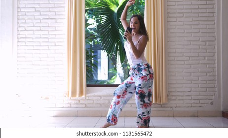 Young cheerful woman in pajamas is dancing next to the window with mobile phone listens to music sings song enjoying the morning.
