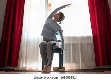 Young cheerful woman practicing yoga, sitting on chair doing side bend exercise, working out at the living room at home
