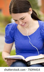 Young cheerful woman reading book and listening to music