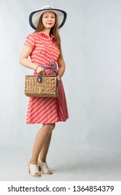 Young cheerful woman in red dress posing with picnic basket in studio on white background