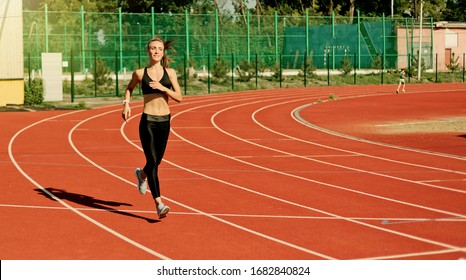 Young cheerful woman runner in sportswear running on stadium track with red coating outdoors