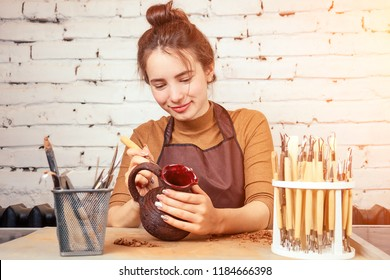 a young and cheerful woman sculpts from clay. The potter works in a pottery workshop with clay. the concept of pottery mastery and creativity
