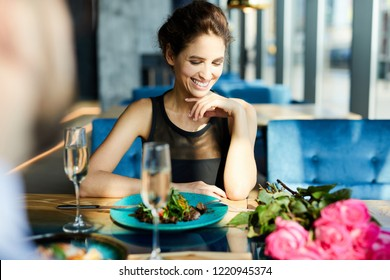 Young cheerful woman sitting by served table and having lunch with her boyfriend in restaurant