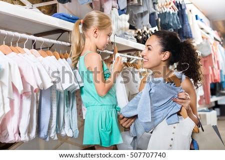 8b5b76851a Young cheerful woman with small girl choosing a blue clothes in a kids apparel  boutique