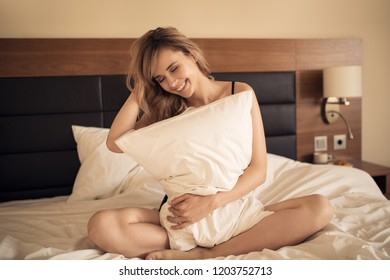 Young cheerful woman smiling in bedroom. Holding pillow in hands.