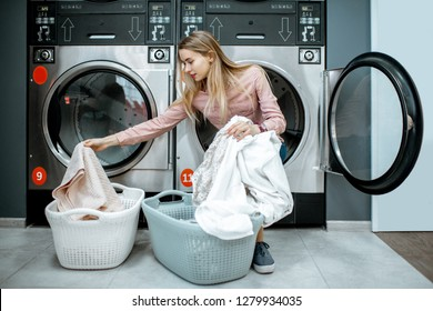 Young and cheerful woman sorting clothes sitting on the dryer machine in the laundry