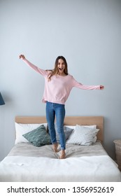 Young cheerful woman standing on the bed at home. Lifestyle concept.